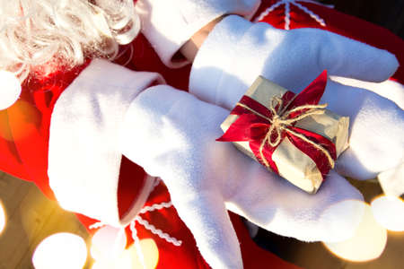 A box with a Christmas gift in the hands of Santa Claus in white mittens. Red suit, beard, garland lights in a blur. New year, preparation, expectation of a miracle, a dream come true. Close up