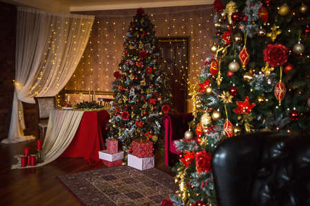 Christmas interior of the dark living room of the house. Christmas tree, lights of garlands on the walls, library Cabinet, books on the shelves. Luxury interior. New Year, red and gold balls.