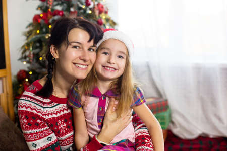 Mom and daughter hug, smile happily and look at the camera, sit at home near the Christmas tree in comfortable clothes and a Santa hat. Christmas, new year's eve at home. Decor, gift boxes, copy space Stok Fotoğraf