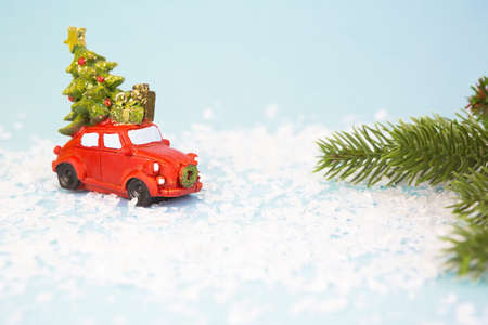 Christmas decor - a red retro car on artificial snow carries a Christmas tree with gift boxes on the roof. Toy with sequins on a blue background, space for text. New Year Stock Photo