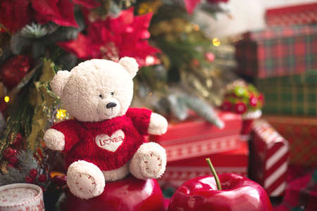 White Teddy bear in red knitted sweater with heart on the chest and the words Love near Christmas tree among the gift boxes. Gift to your beloved, Declaration of love, poinsettia decor. Copy space