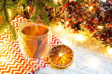 Transparent double-walled glass tumbler with hot tea and cinnamon sticks on the table with Christmas decor. New year's atmosphere, slice of dried orange, garland and tinsel, spruce branch, cozy