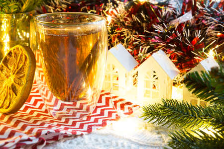 Transparent double-walled glass tumbler with hot tea and cinnamon sticks on the table with Christmas decor and small house. New year's atmosphere, slice of dried orange, garland, spruce branch, cozy