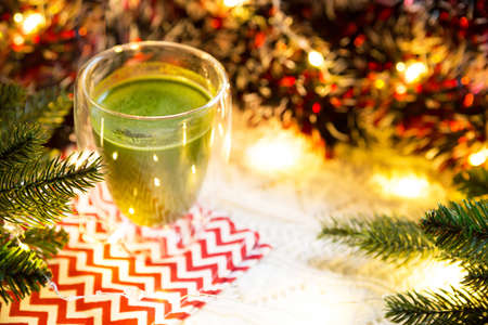 Transparent double-walled glass tumbler with Japanese matcha tea on table with Christmas decor. New year's atmosphere, garland and tinsel, spruce branch, cozy, knitted blanket, ball, striped napkin
