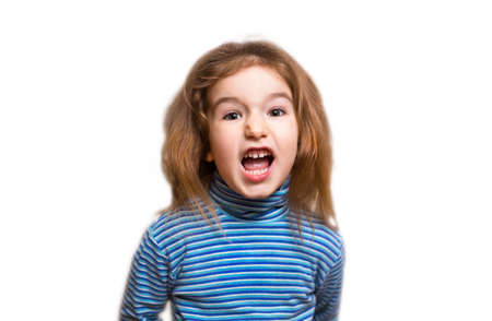 A small Caucasian girl in a blue striped turtleneck opened her mouth in indignation and twisted her face, wrinkling her nose. Denial, unpleasant, outrage, phew, disgusting. White background, isolate
