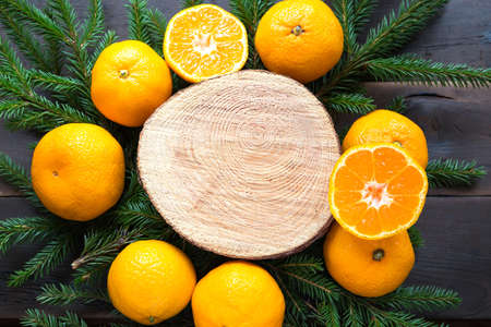 New year's holiday background on round cut of tree surrounded by tangerines, live fir branches and golden lights garlands, with wooden space for text. Citrus aroma, slices of orange, Christmas. frame