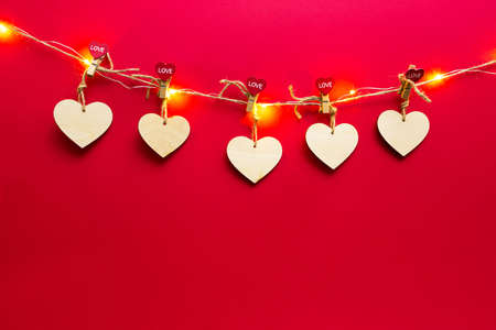 Garland of wooden hearts with clothespins with the inscription LOVE on a red background. Valentine's day, copy space, mock up. Holiday lights, flyer, lovers