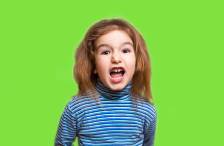 A small Caucasian girl in a blue striped turtleneck opened her mouth in indignation and twisted her face, wrinkling her nose. Denial, unpleasant, outrage, phew, disgusting. Green background, copyspace