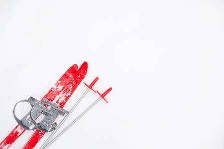 Children's red skis with sticks -layout in the snow. Children's winter sport, outdoor activities, family fun. White natural frosty background. Copy space.