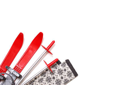 Children's red cross country skis with sticks and scarf with snowflakes - layout in white background. Winter sport, outdoor activities, family fun. Copy space, flat lay.