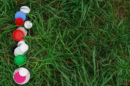 Colorful plastic bottle caps on the green grass. Volunteer charity event