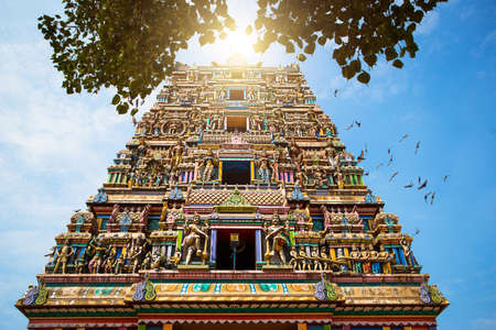 Traditional Hindu temple Kidangamparambu Sree Bhuvaneswari in India in Allapuzha (Allepi) Kerala. Tall building with colorful figures of Indian mythology and gods, flock of live birds. Tourism, travel