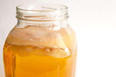 Kombucha-a drink made from tea mushroom in a glass jar with a tap. Transparent mug with a yeast drink made from a Japanese mushroom-jellyfish. White background, healthy food. Copy space