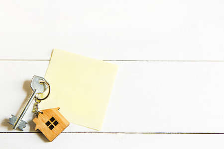 Keychain in the shape of wooden house with key on a white background with a square sheet for notes. Building, design, project, moving to new house, mortgage, rent and purchase real estate. Copy space