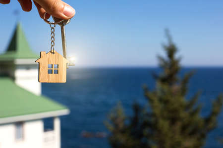 Wooden pendant of a house and key. Background of sea, fir tree and cottage. House and life on ocean, construction, project, moving to new house, mortgage, rent and purchase of real estate. Copy space Imagens