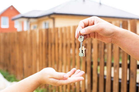 Hand with a key and a wooden key ring-house. Background of fence and cottage. Building, project, moving to a new home, mortgage, rent and purchase real estate. To open the door. Copy space