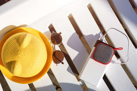 Music portable speaker is charged from the power bank via usb on a deck chair near the pool with beach accessories. Always in touch, travel gadgets, external battery for a smartphone. Place for text. Flatlay