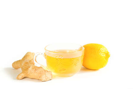 Medicinal tea in a cup, ginger, lemon-strengthen the immune system in the cold season. Vitamin drink for health and ingredients on a white background.