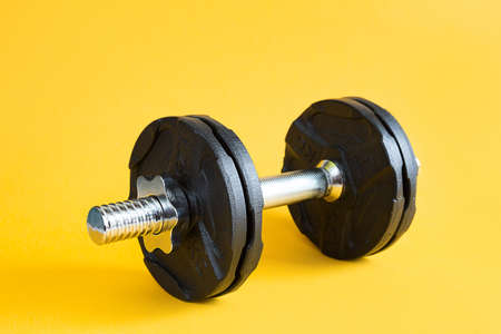 Dumbbell with disks on a yellow background close-up. Sports lifestyle, strength training, gym. Copy space Standard-Bild