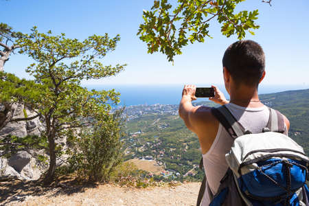 Male tourist takes photos on a smartphone of beautiful view of sea in a mountainous area from the top among coniferous trees. Video communication, using the phone when traveling. SIM card in roaming
