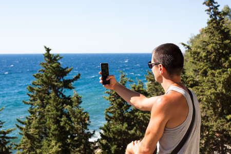 Male tourist takes photos on a smartphone of beautiful view of sea in a mountainous area from the top among coniferous trees. Video communication, using the phone when traveling. SIM card in roaming Reklamní fotografie