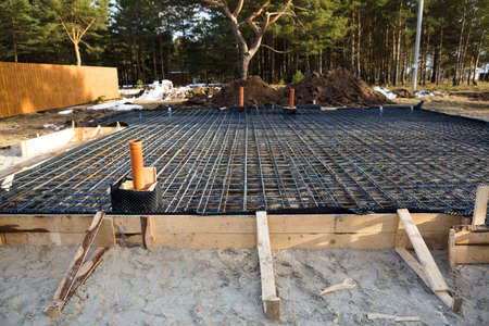 Iron fittings on a wooden blind area with laid pipes are the basis for pouring the foundation of the house with a concrete slab. Construction of cottages, design, engineering communications.