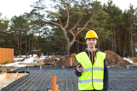 Construction worker talks on a smartphone in a yellow helmet and protective vest against the background of the construction of house-reinforcement for the foundation, pipes and blind area.