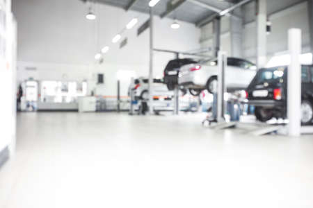 Car repair service in defocus, industrial background. Cars on lifts, transport service area, the mechanic repairs the car. Copy space Reklamní fotografie