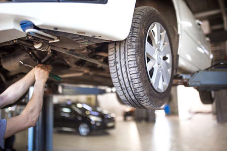 The car is lifted for repair on a lift in a car service station, a mechanic in overalls repairs in the background. Wheel close-up, tire service Banque d'images