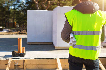 The project architect's back is on the construction site of a house with the foundation laid and the blocks delivered. Construction worker in a protective yellow helmet and a signal vest. Mock up