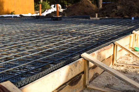 Iron fittings on a wooden formwork with laid pipes are the basis for pouring the foundation of the house with a concrete slab. Construction of cottages, design, engineering communications. Stock Photo
