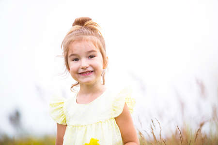 Portrait of a cute girl in field with a wild flower. Childhood, holidays in the country, freedom and carelessness. Summer time. International Children Day. Mosquito repellent, cottage core. Copy space