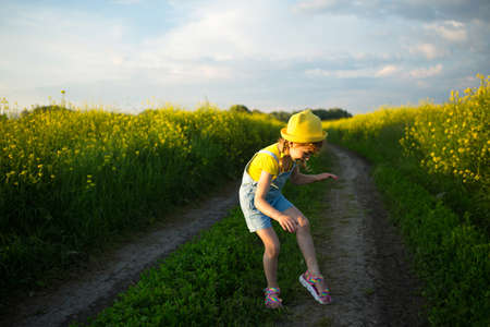 Girl in a field kills mosquitoes that bite her hands and feet. The child slaps himself on the body, protection from insect bites, repellent safe for children. Outdoor recreation, against allergies