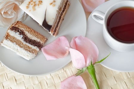Closeup of cake with romantic roses and cup of tea photo