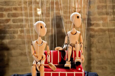 Wooden marionettes sit on the red couch Stock Photo