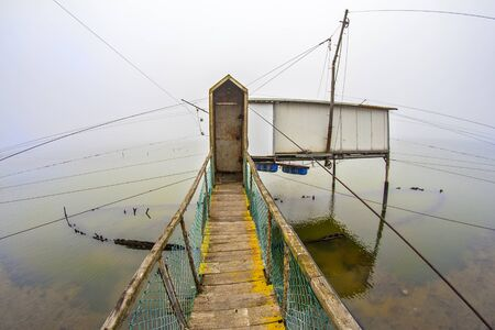commercial fishing net: Fishing huts on the sea near the city of Comacchio in Italy during a foggy day.