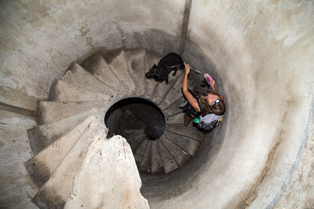 Woman with dog on the spiral staircase in a military bunker on Polog, Slovenia