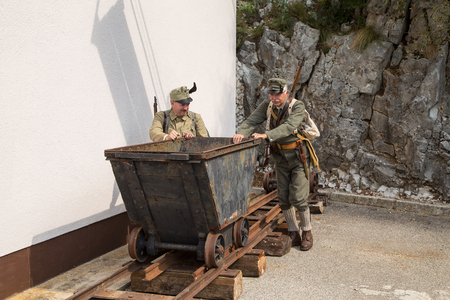 one armed: Austro-Hungarian soldiers of the World War one push trolley on the Event Peace march 2016 on the mountain Sabotin, Slovenia.
