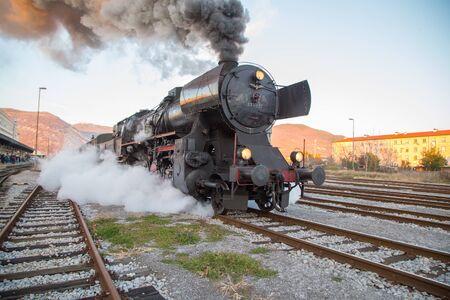 Nova Gorica, Slovenia - December 17, 2017: Old steam train leaving the railway station of  Nova Gorica, Slovenia, lots of black and gray steam Editorial