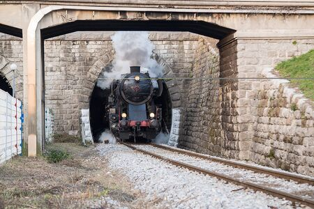 Old steam train leaving the railway station of  Nova Gorica, Slovenia, lots of black and gray steam Stock Photo