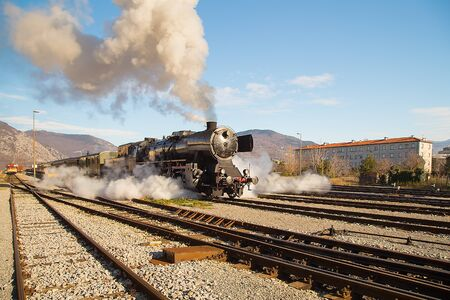Old steam train leaving the railway station of  Nova Gorica, Slovenia, lots of black and gray steam Editorial