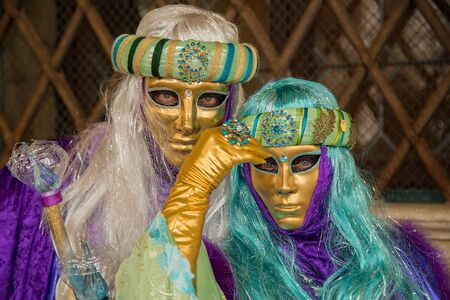 Venice, Italy - February 22, 2017: Traditional Venetian Carnival Masks on St. Mark's Square in Venice. Portrait of a man and woman wearing a mask in Venice during the carnival days. Editorial