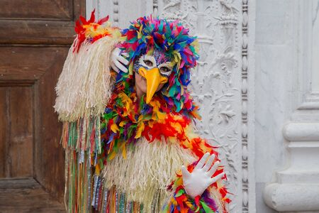 Venice, Italy - February 22, 2017: Single traditional Venetian mask on St. Mark's Square in Venice. Portrait of a woman wearing a mask in Venice during the carnival days