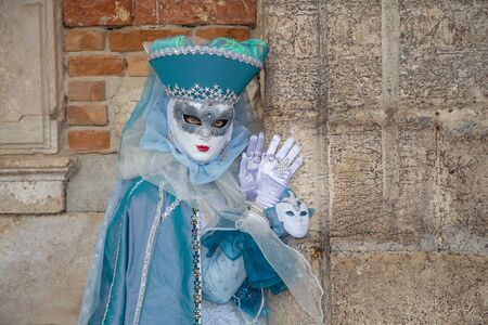 Venice, Italy - February 22, 2017: Single traditional Venetian mask on St. Mark's Square in Venice. Portrait of a woman wearing a mask in Venice during the carnival days.