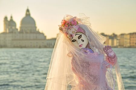 Venice, Italy - February 10, 2015: Single traditional Venetian mask on St. Mark's Square in Venice. Portrait of a woman wearing a mask in Venice during the carnival days.