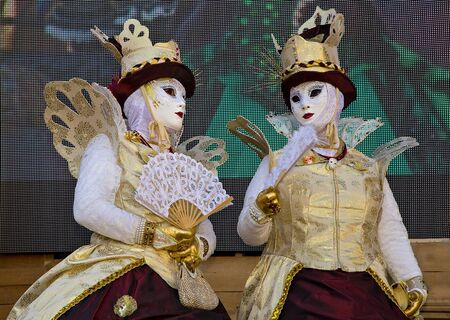 Venice, Italy - February 10, 2015: Traditional Venetian Carnival Masks on St. Mark's Square in Venice. Portrait of a man and woman wearing a mask in Venice during the carnival days.