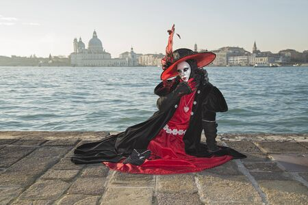 Venice, Italy - February 10, 2015: Single traditional Venetian mask on St. Marks Square in Venice. Portrait of a woman wearing a mask in Venice during the carnival days.
