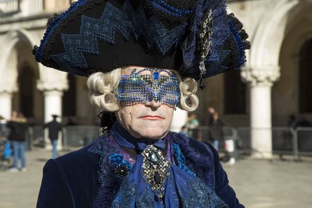 Venice, Italy - February 10, 2015: Single traditional Venetian mask on St. Mark's Square in Venice. Portrait of a man wearing a mask in Venice during the carnival days.