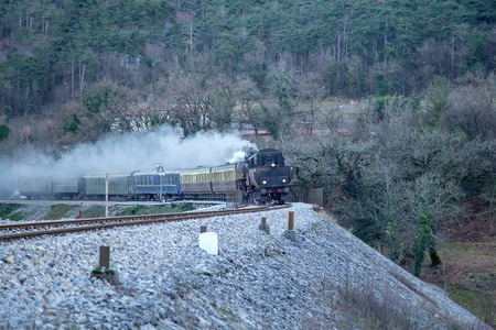 Old steam train on the railway station of  Branik, Slovenia, lots of black and gray steam Stock Photo