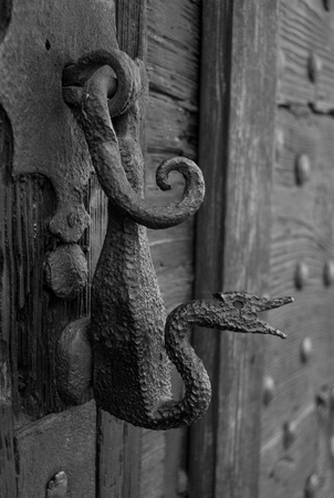Original metal knocker on an old wooden door in black and white Stock Photo